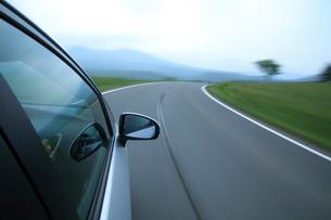 新緑の道を走るハイブリッドカーの写真素材 [FYI01451433]