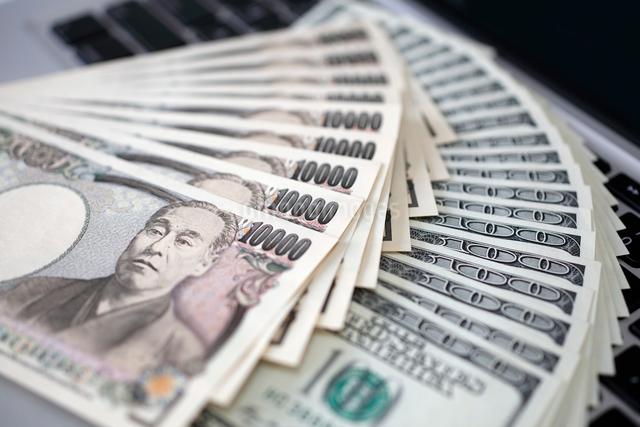 ノートパソコンのキーボードと1万円札と100ドル札の写真素材 [FYI01451530]