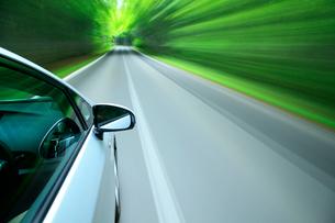 新緑の道を走るハイブリッドカーの写真素材 [FYI01451578]