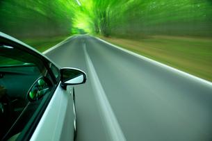 新緑の道を走るハイブリッドカーの写真素材 [FYI01451620]