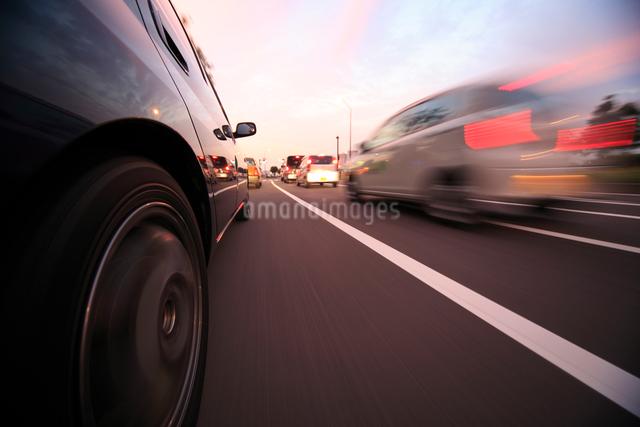 夕暮れの街を走る車のタイヤの写真素材 [FYI01451710]