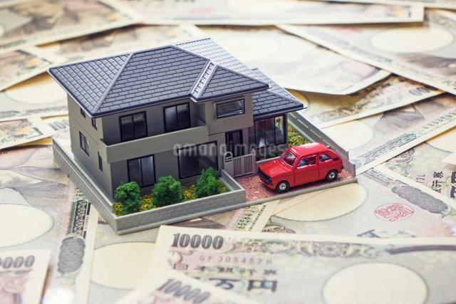 一面の一万円札と家の模型と赤い車の写真素材 [FYI01453066]