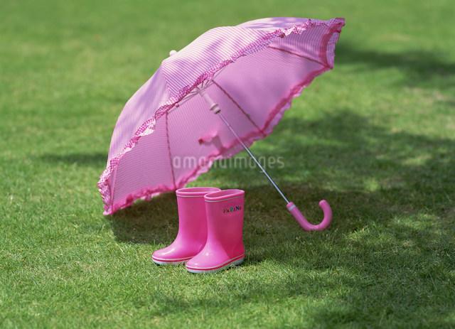 子供用のピンクの傘と長靴の写真素材 [FYI01453953]