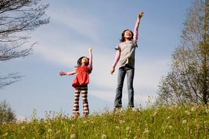 タンポポ畑でジャンプする二人の女の子(姉妹)の写真素材 [FYI01455872]