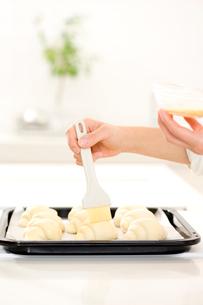 ロールパンに卵黄を塗る女性の手の写真素材 [FYI01456037]