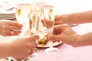 シャンパンで乾杯をする手とオードブルの写真素材 [FYI01456082]