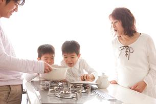 ガスキッチンを囲む親子の写真素材 [FYI01456217]