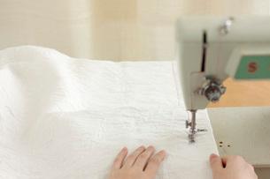 古いミシンで白い布を縫う手の写真素材 [FYI01456220]