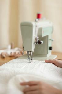 古いミシンで白い布を縫う手の写真素材 [FYI01456272]
