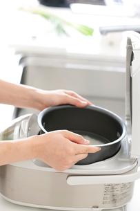 米を炊飯器に入れる女性の手元の写真素材 [FYI01456308]