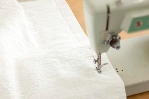 古いミシンで白い布を縫うの写真素材 [FYI01456440]