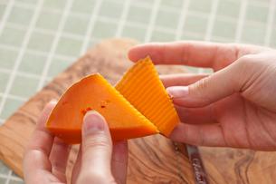 オリーブのまな板でチーズを切る手の写真素材 [FYI01456696]