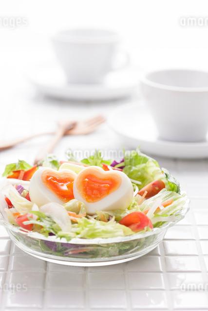 ふたつに切ったハート型のゆで卵の入ったサラダの写真素材 [FYI01457082]