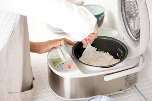 炊飯器の米を混ぜる手元の写真素材 [FYI01458085]