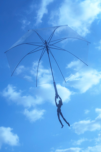 空飛ぶビニール傘と人形の写真素材 [FYI01458475]