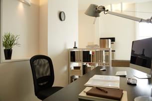 白い部屋の机と本棚机のうえに書類とパソコンの写真素材 [FYI01458510]