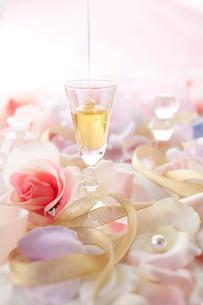 グラスに注がれるはちみつとピンクのバラとリボンの写真素材 [FYI01458536]