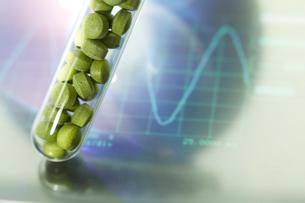 モニターの上のビタミン錠剤の入った試験管の写真素材 [FYI01458558]