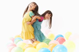 風船と背中合わせの双子の姉妹の写真素材 [FYI01458584]