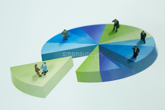 円グラフの上に立つ沢山のサラリーマンの人形の写真素材 [FYI01458620]