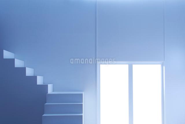 窓から光の入る明るく白い部屋と階段の写真素材 [FYI01458628]