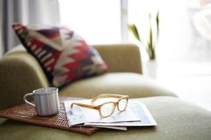 明るいリビングにあるソファーとメガネとマグカップの写真素材 [FYI01458650]
