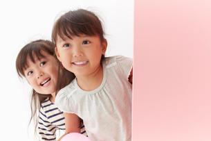 ピンク色の壁から顔を出す双子の姉妹の写真素材 [FYI01458763]