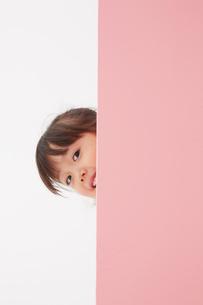 ピンク色の壁から顔を出す女の子の写真素材 [FYI01458792]