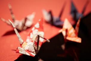 紅白の天板のうえの千代紙で折られた数羽の鶴の写真素材 [FYI01458807]