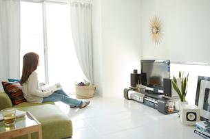明るいリビングのソファーに座る女の人の写真素材 [FYI01458821]