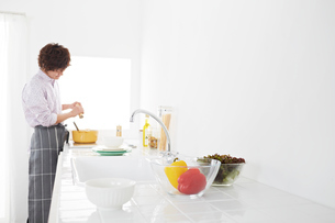 キッチンで味付けをするエプロン姿の男性の写真素材 [FYI01458871]