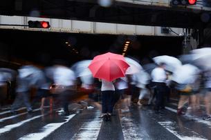 歩道で傘を持ってたたずむ女性の写真素材 [FYI01458887]
