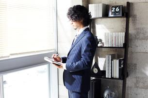 窓辺に立ち手帳に書くビジネスマンの写真素材 [FYI01458896]