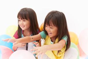 風船で遊ぶ双子の姉妹の写真素材 [FYI01458981]