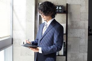 窓辺に立ち手帳に書くビジネスマンの写真素材 [FYI01458990]