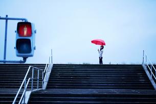 川の土手の階段前で傘を持ってたたずむ女性の写真素材 [FYI01459003]