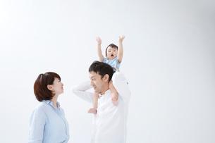 両手を上げている赤ちゃんを肩車しているお父さんとお母さんの写真素材 [FYI01459047]