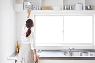 キッチンの戸棚から物を取る女性の写真素材 [FYI01459166]