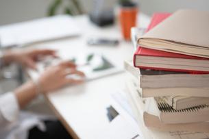 机の上の山積みの本とタブレット端末を持つ女性の手の写真素材 [FYI01459171]