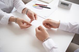 机の上で名刺交換をする2人の女性の手の写真素材 [FYI01459195]