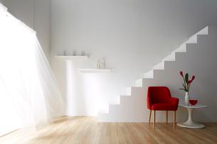 光の入る明るく白い部屋にある白い階段と風でなびくレースカーテンの写真素材 [FYI01459245]