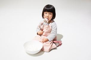 エプロンをしてクリームをなめる女の子の写真素材 [FYI01459289]