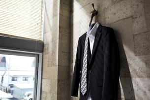 壁のハンガーに掛かるスーツとネクタイの写真素材 [FYI01459309]