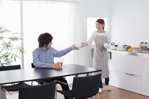 キッチンに立つ女性から料理をダイニングの椅子に座り受け取る男性の写真素材 [FYI01459388]