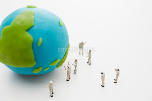 粘土の地球儀と作業着姿の沢山の人形の写真素材 [FYI01459414]