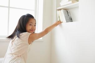 窓辺の本箱から本を取る女の子の写真素材 [FYI01459418]