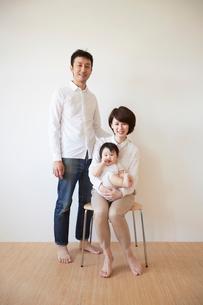 赤ちゃんを膝の上に座らせて椅子に座るお母さんと後ろで立っているお父さんの写真素材 [FYI01459431]
