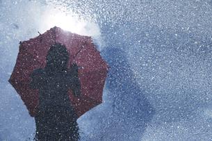道路の水溜りに傘を持って写りこんでいる女性の写真素材 [FYI01459575]