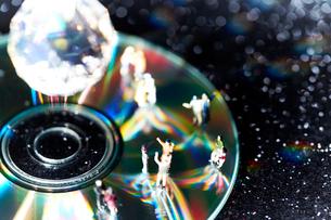 DVDディスクの上で踊る沢山の人形の写真素材 [FYI01459596]