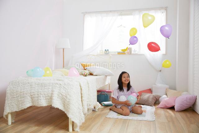 子供部屋のベッドの横でフーセンで遊ぶ女の子の写真素材 [FYI01459626]